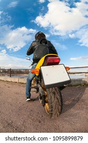 Wide angle view at the back of yellow motorcyclist on bike with clear blank license plate