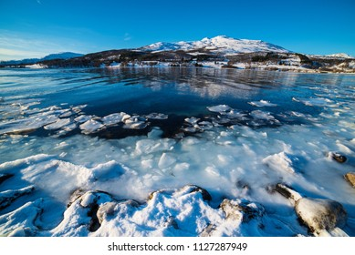 Wide angle view of beautiful winter lake with snowy mountains at Lofoten Islands in Northern Norway