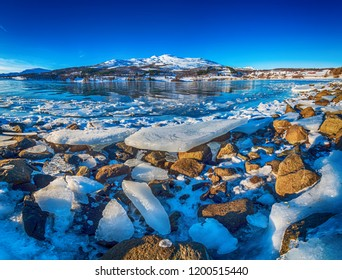 Wide angle view of beautiful winter lake with ice on the coast at Lofoten Islands in Northern Norway