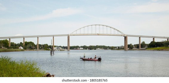 Wide angle view of the Chesapeake and Delaware Canal (C and D canal) at the Back Creek section in Chesapeake City, MD. An old metal arched bridge is on the canal.  A couple is fishing on a boat