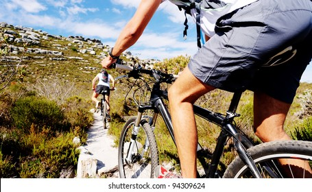 Wide angle view of a cyclist riding a bike on a nature trail in the mountains. two people living a healthy lifestyle
