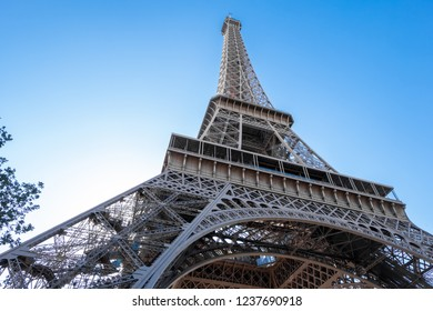 Wide angle view to Eiffel Tower from the buttom. Scale of the building idea. Blue sky with harsh light. Paris, France