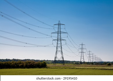A wide angle view of Electricity Pylons crossing along a green field in East Sussex, England.