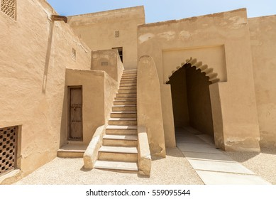 Wide angle view of the entrance of Riffa Fort, Bahrain from the courtyard on a sunny day. A stone staircase leads through adobe walls with a door and lattices for ventilation to rooms above.