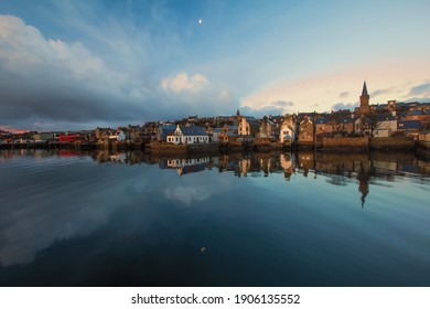 Wide angle view of fishing town Stromness on Orkney islands with moon reflecting in water and distandt stone buildings at sunrise - Shutterstock ID 1906135552