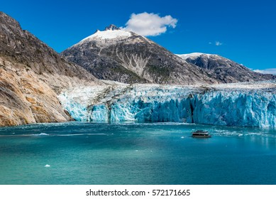 Wide angle view of glacier face with tourist boat and snow capped mountains and dappled sunshine on the icy waters