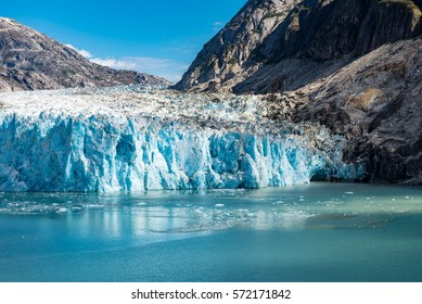 Wide angle view of glacier face with blue ice and dappled sunshine across the water