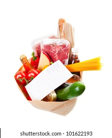 Wide angle view of a grocery bag full of barbecue staples with a hand written grocery list on top.
