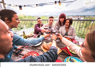 Wide angle view of happy people toasting red wine together at rooftop party in open air villa - Young friends eating bar-b-q food at restaurant patio - Cool friendship concept on warm vivid filter