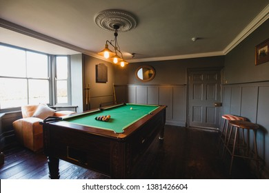 Wide angle view of an interior of a games room in a house.