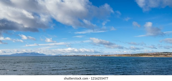 A wide angle view looking out from Stevenston foreshore to Saltcoats and Ardrossan with Arran in the hazy distance.