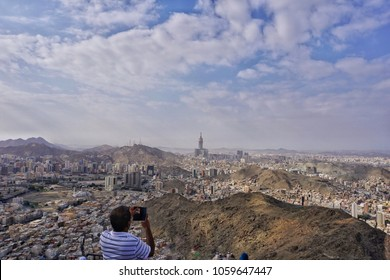Wide angle view of Mecca town from the top of Jabal Nur and a tourist capturing a photo of it using his smartphone.