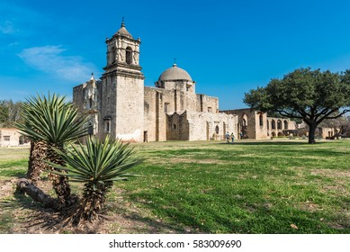 Wide angle view of Mission San Jose in the background with cacti plants in the foreground