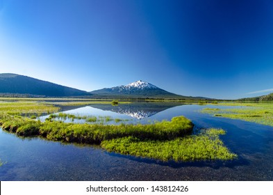 A wide angle view of Mount Bachelor being perfectly reflected in a lake near Bend, Oregon