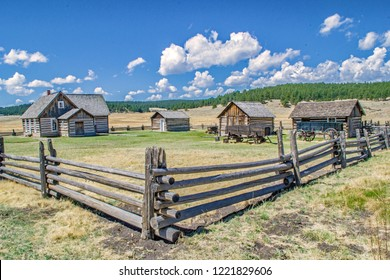 Wide angle view of an old west homestead with log cabins surrounded by a wooden fence in a valley on a sunny summer day.