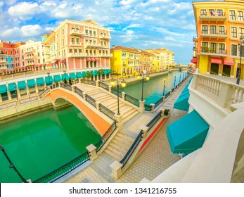 Wide angle view of panoramic bridge in Venice at Qanat Quartier in the Pearl, Persian Gulf, Middle East at sunset. Aerial view picturesque and luxurious district icon of Doha, Qatar, in venetian style