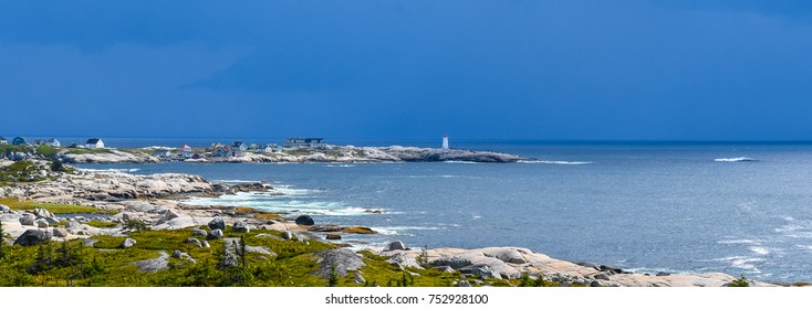 A wide angle view of the Peggy's Cove lighthouse on the coast of Nova Scotia