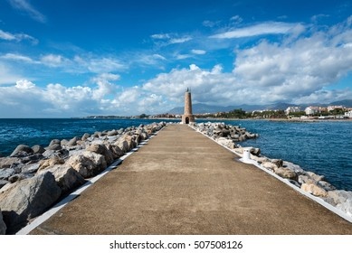 Wide angle view of the pier leading to one of the stone lighthouses at the marina of Puerto Jose Banus on the Costa del Sol on a cloudy Autumn morning,