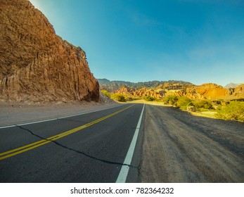 """wide angle view of a road surrounded by rocks and vegetation, with blue sky in the background, in the """"Salta"""" province of northern Argentina, south America"""