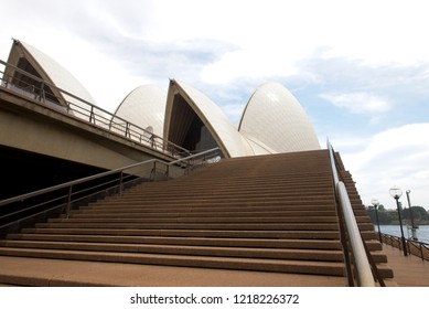 Wide angle view of sails of Sydney Opera House with nobody on stairs, blue sky and clouds as background.