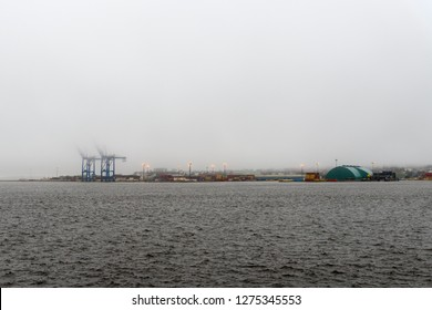 Wide angle view of Saint John harbor at high tide.The water is so high that it is almost over the docks. The top of the cranes are hidden by fog. Lots of room for text.
