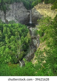 A wide angle view showing a natural gorge and amphitheater with a dramatic waterfall.