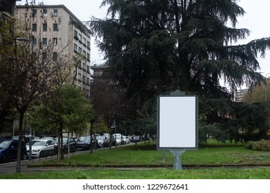 Wide angle view of small blank white outdoor advertising billboard in green area of a city