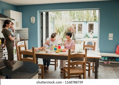 Wide angle view of three mid adult mothers sitting at a kitchen table talking. Two of the mothers have their children with them and enjoying some snacks.