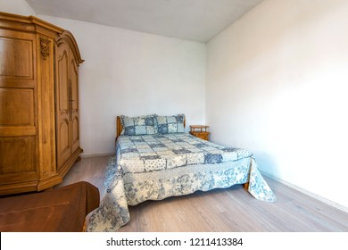 Wide angle view of a traditional English bedroom in white with patchwork quilts