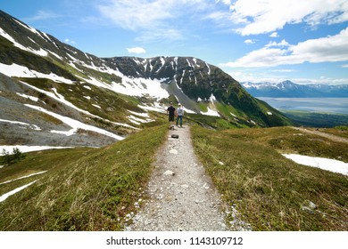 Wide Angle View of Two People Standing at the Edge of a Trail Looking Out over Girdwood Alaska