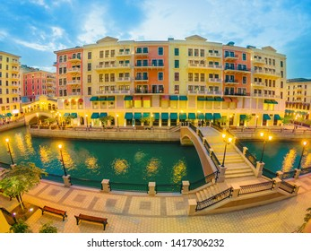 Wide angle view of two Venetian bridges on canals of picturesque district icon of Doha illuminated at night. Panorama of Venice at Qanat Quartier, the Pearl-Qatar, Middle East. Twilight shot.