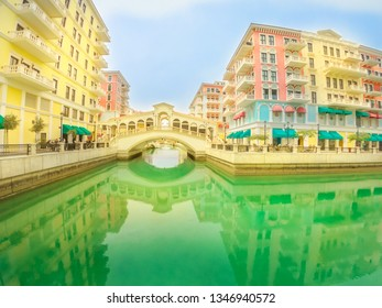 Wide angle view of Venice bridge at Qanat Quartier in the Pearl-Qatar, Persian Gulf, Middle East. Venetian bridge reflecting on canals of picturesque and luxurious district of Doha, Qatar.