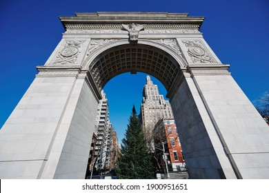 wide angle view of Washington Square Arch from ground up to clear blue sky. The Tuckahoe marble bas relief details show an eagle and two coats of arms. Midtown New York skyscrapers in background.