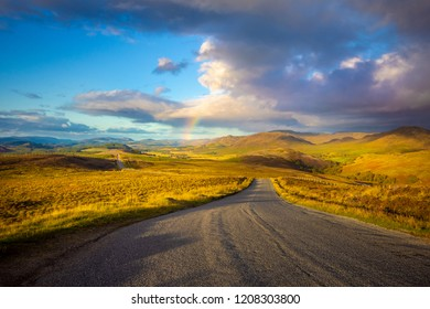 Wide angle view of winding road in the highlands of Scotland with a rainbow. General Wade's curvy Military Road, follows the line of the military road build in the 1700s with mountain view. Empty road