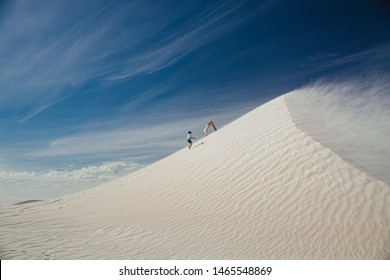 Wide angle view of a young boy and his mother climbing a sand dune at Lancelin Dunes. They are climbing up with sand boards, ready to sandboard down the dune.