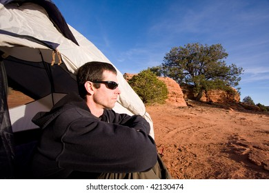 Wide angle view of young man sitting inside tent in Arizona desert. Outdoor adventure/camping concept.