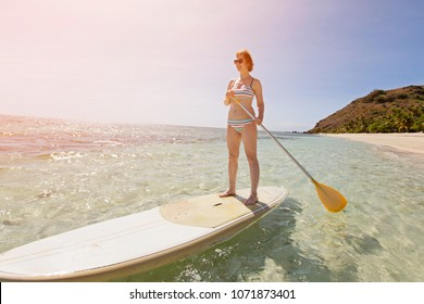 wide angle view of young woman enjoying stand up paddleboarding in beautiful turquoise lagoon at tropical island, active vacation concept, sun glare