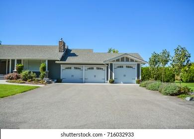 Wide asphalt driveway of residential house with three doors garage