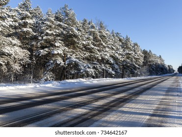wide asphalt road, on which there are ruts from cars on the roadway. Photo taken in the forest in the winter season. Blue sky in the background