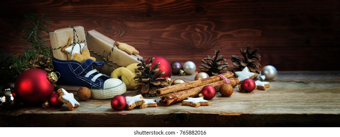 Wide background for St. Nicholas Day, Children's shoe with sweets and gifts on December 6th on rustic wood, german christmas consumption called Nikolaus, panoramic format, copy space, selected focus
