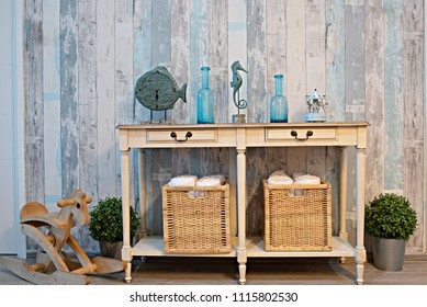 Wide of Background texture hardwood in living room decoration with the bottle, fish clock, tree busket, rocking horse, towel basket under the table. Paint wall, Blue and brown pillow, sea concept.