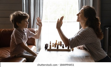 Wide banner panorama image view of excited young Caucasian mom and little son give high five after chess set. Happy mother and small boy child celebrate win in board game. Kid development concept.