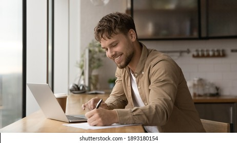 Wide banner panoramic view of smiling young Caucasian man sit at desk make notes working online on computer. Happy millennial male handwrite study distant on laptop in office. Education concept.