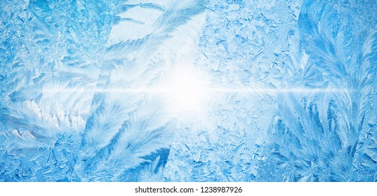 Wide blue winter background, collage of frozen icy windows, cold sunny weather, bright sun shines through frozen window, weather forecast concept