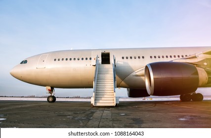 Wide body passenger airplane with a boarding stairs at the airport apron in the evening sun