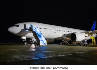 Wide body passenger airplane with boarding ramp at the night airport apron. Aircraft ground handling