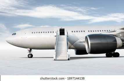 Wide body passenger airplane with a boarding steps at the airport apron isolated on bright background with sky