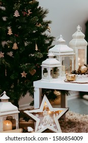wide christmas background with a candle light lantern, baubles, cinnamon stars, cones and snoe on rustic bright wood, panorama format for website banner, copy space, selected focus