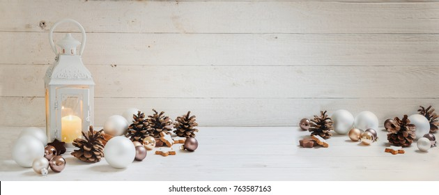 wide christmas background with a candle light lantern, baubles, cinnamon stars and cones on rustic white wood, panorama format for website banner, copy space, selected focus