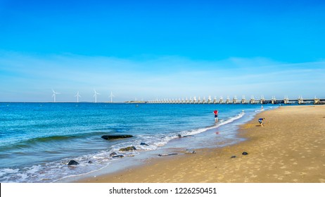 The wide and clean sandy beach at Banjaardstrand along the Oosterschelde inlet at the Schouwen-Duiveland peninsula in Zeeand province in the Netherlands. The Storm Surge Barrier in the backgroud